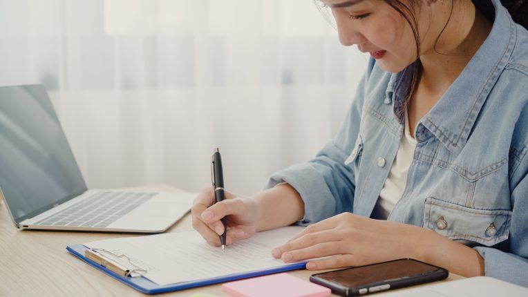 Jeune entrepreneur en train de prendre des notes à côté de son ordinateur